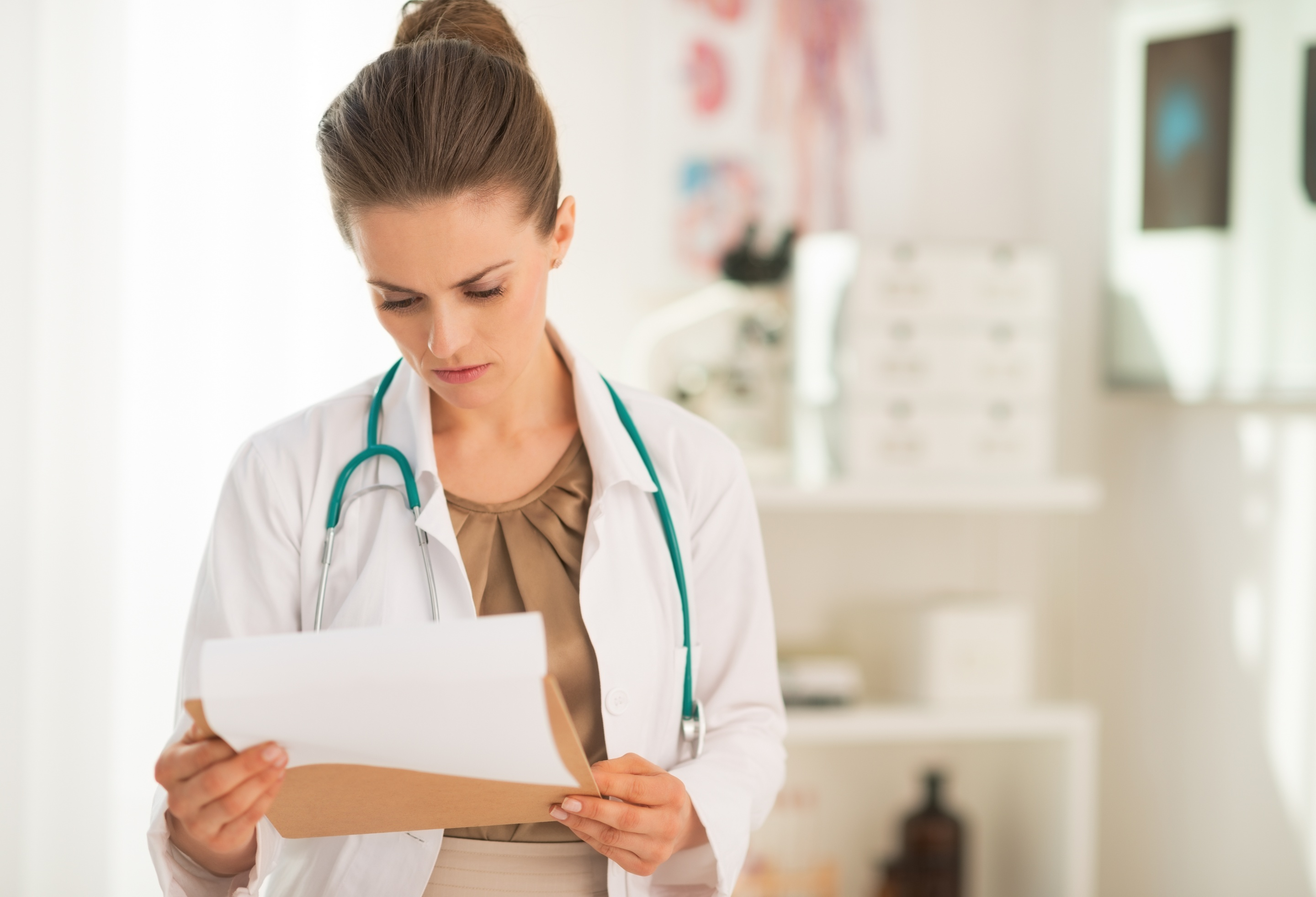 Medical doctor woman looking in clipboard
